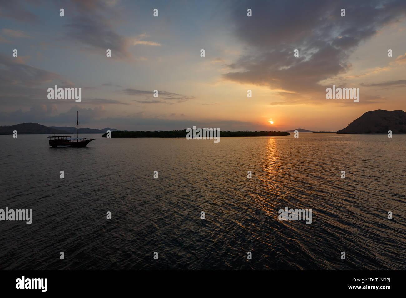 passengers on ferry goinging to Komodo Isalnd enjoy beautiful sunset on water - Stock Image