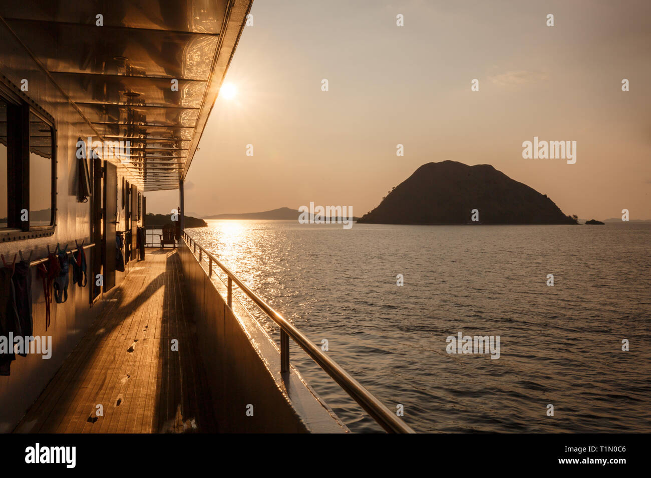 passengers taking ferry  to Komodo Island enjoy beautiful sunset on water - Stock Image
