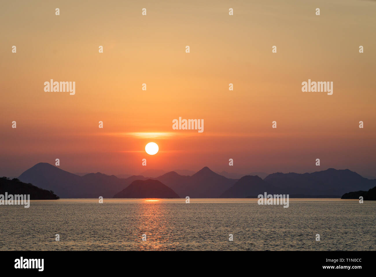Sunset over the jagged mountains in Nussa Tenggara reflects on a calm sea - Stock Image