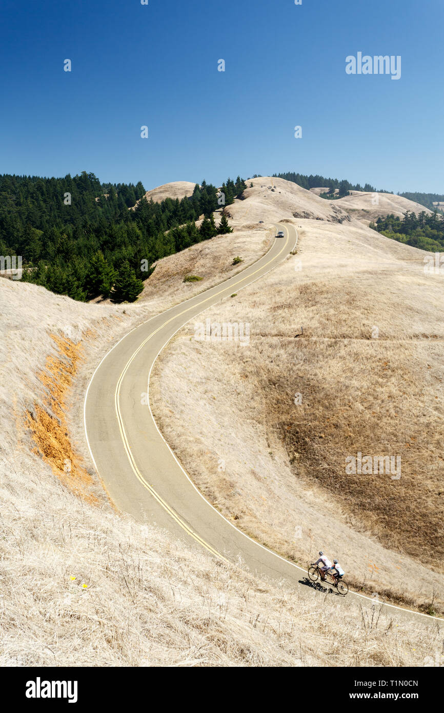 Single car followed by cyclists on a tandem bike travel up dry brown hills of Marin County in hot summer - Stock Image