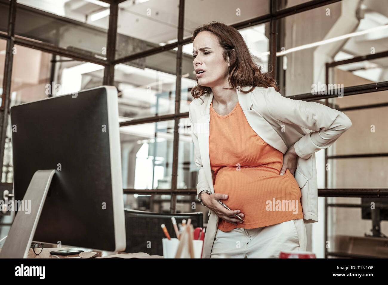 Unstable dark-haired pregnant woman holding her stomach and back - Stock Image