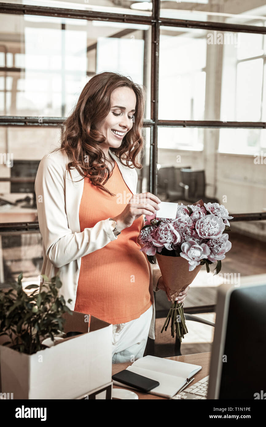 Contented attractive expecting woman being happy with flowers - Stock Image
