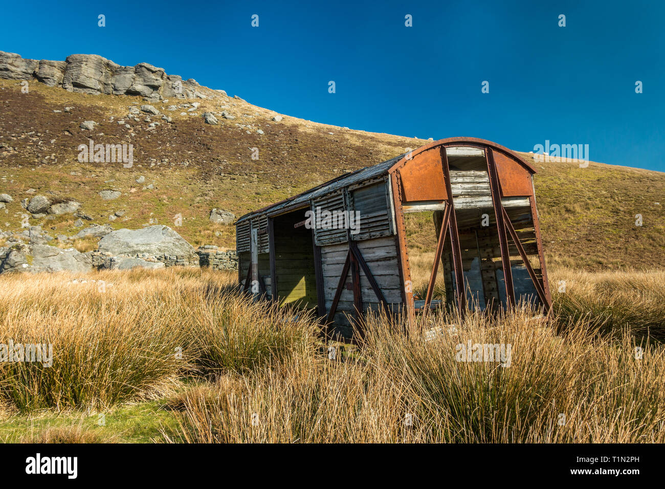 Upcycled railway goods carriage, now shed or barn, in beautiful light and blue sky on the moorland road, between Nateby and Thwaite in Upper Swaledale - Stock Image
