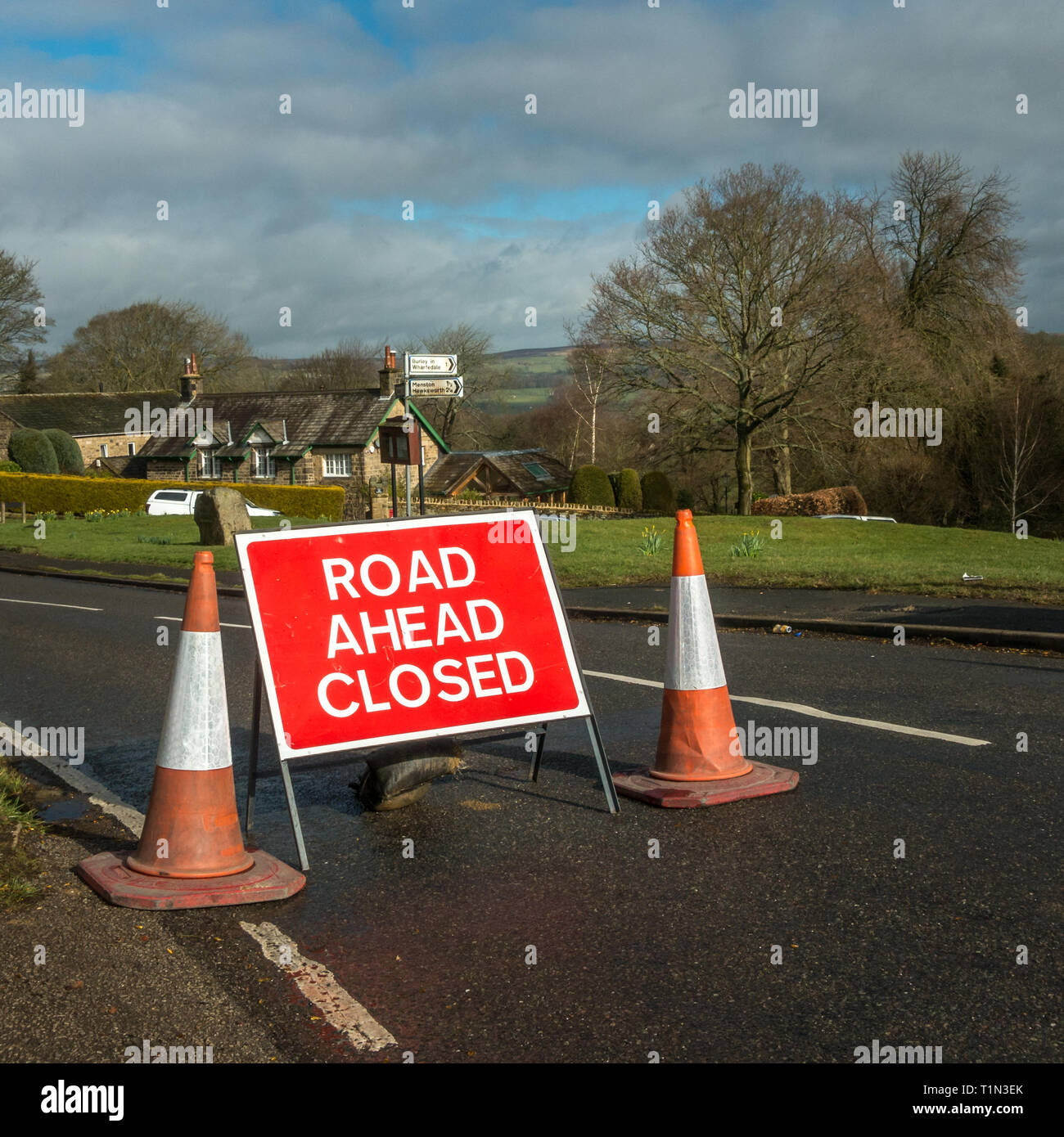Road block with road ahead closed sign and traffic cones at Burley Woodhead leading to Ilkley, over Ilkley moor, West Yorkshire, UK - Stock Image