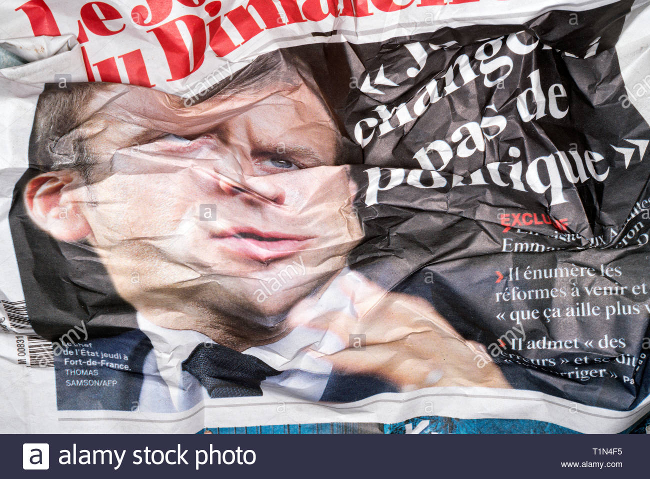 crumpled newspaper with portrait of French president Emmanuel Macron - Stock Image