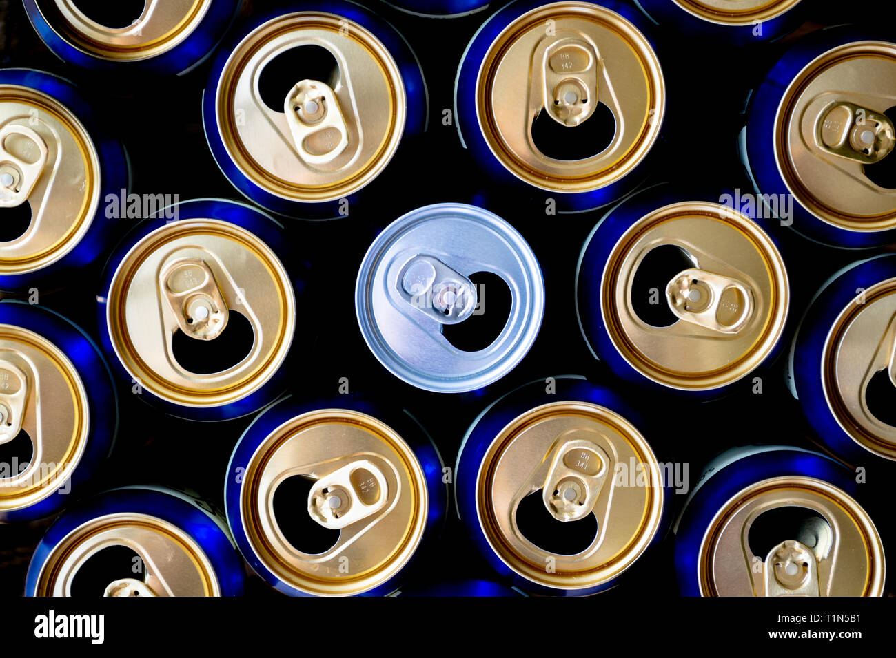 Abstract pattern of opened aluminium cans, top view. One white soda or beer can standing out among yellow and blue cans. Excess drinking, consumerism, - Stock Image