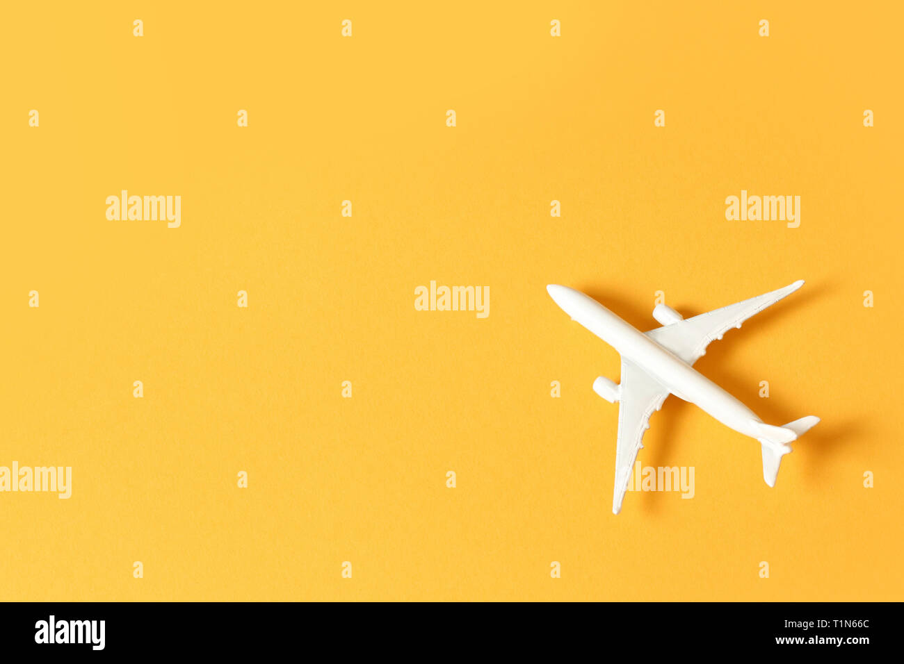 White toy airplane on a yellow background with copy space Stock Photo