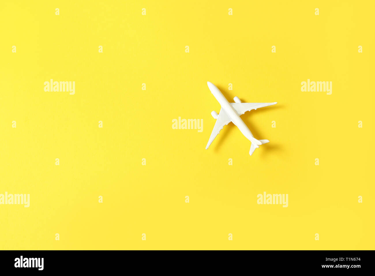 White toy airplane on a yellow background with copy space - Stock Image
