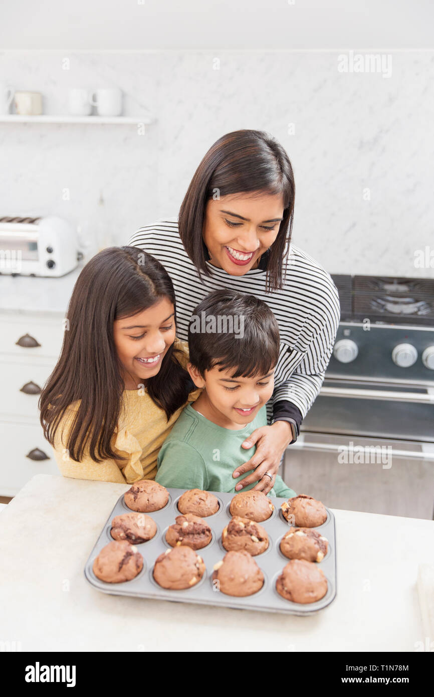 Mother and children baking chocolate muffins in kitchen Stock Photo