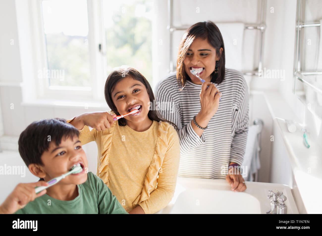 Portrait happy family brushing teeth in bathroom Stock Photo