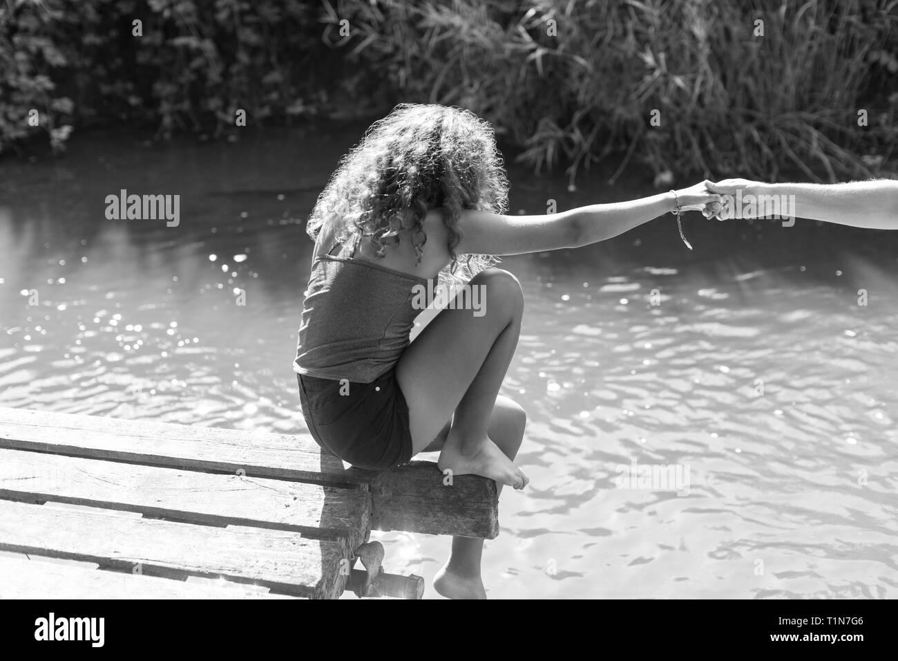 Girl sitting at the edge of sunny riverside dock Stock Photo