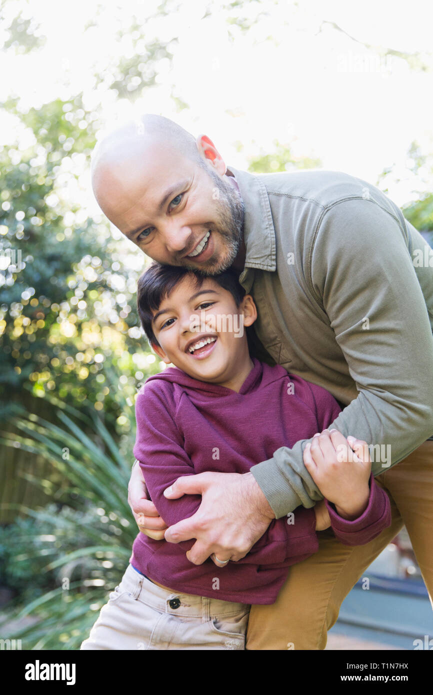 Portrait happy father and son hugging Stock Photo