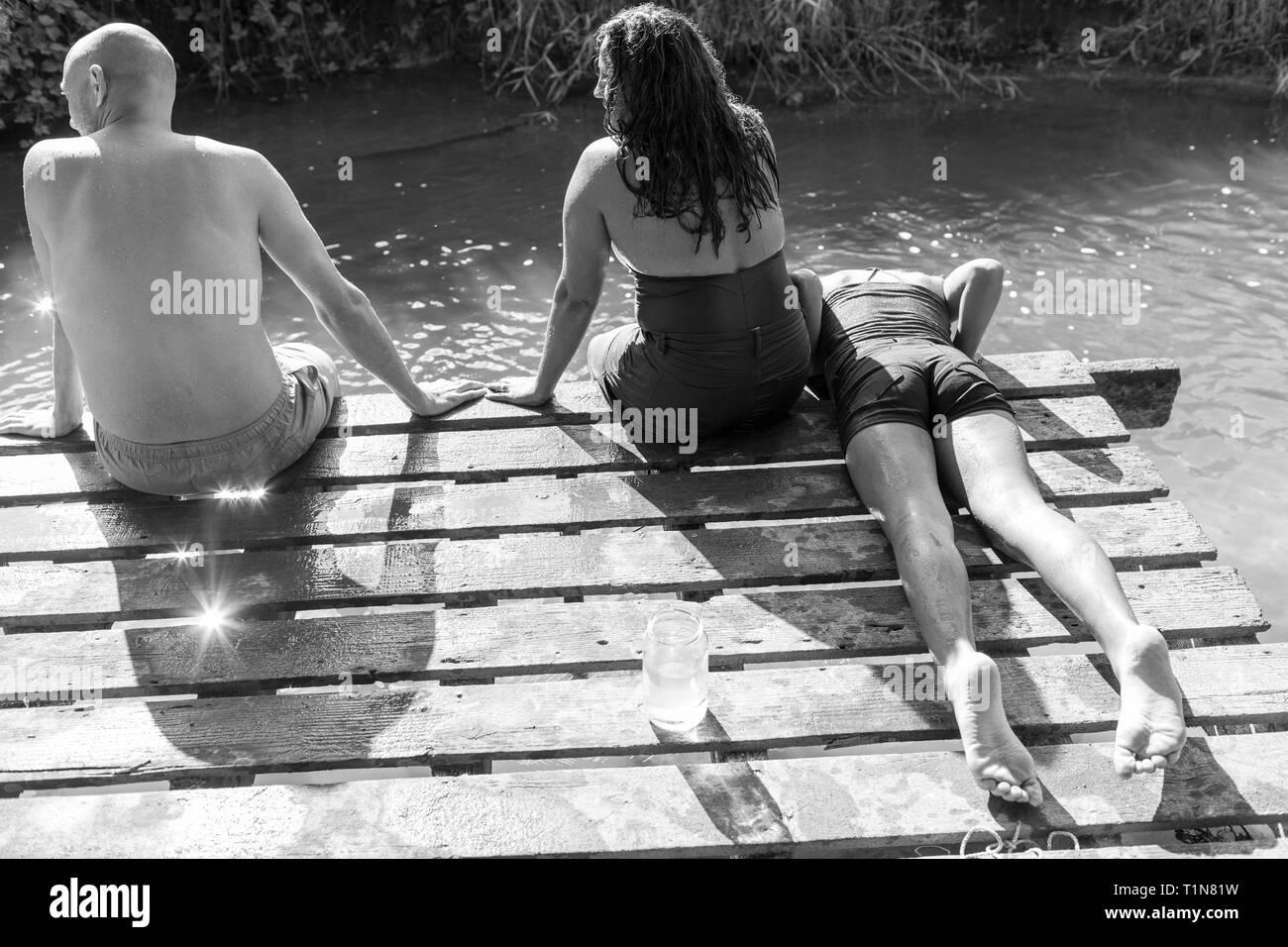 Family relaxing on riverside dock Stock Photo