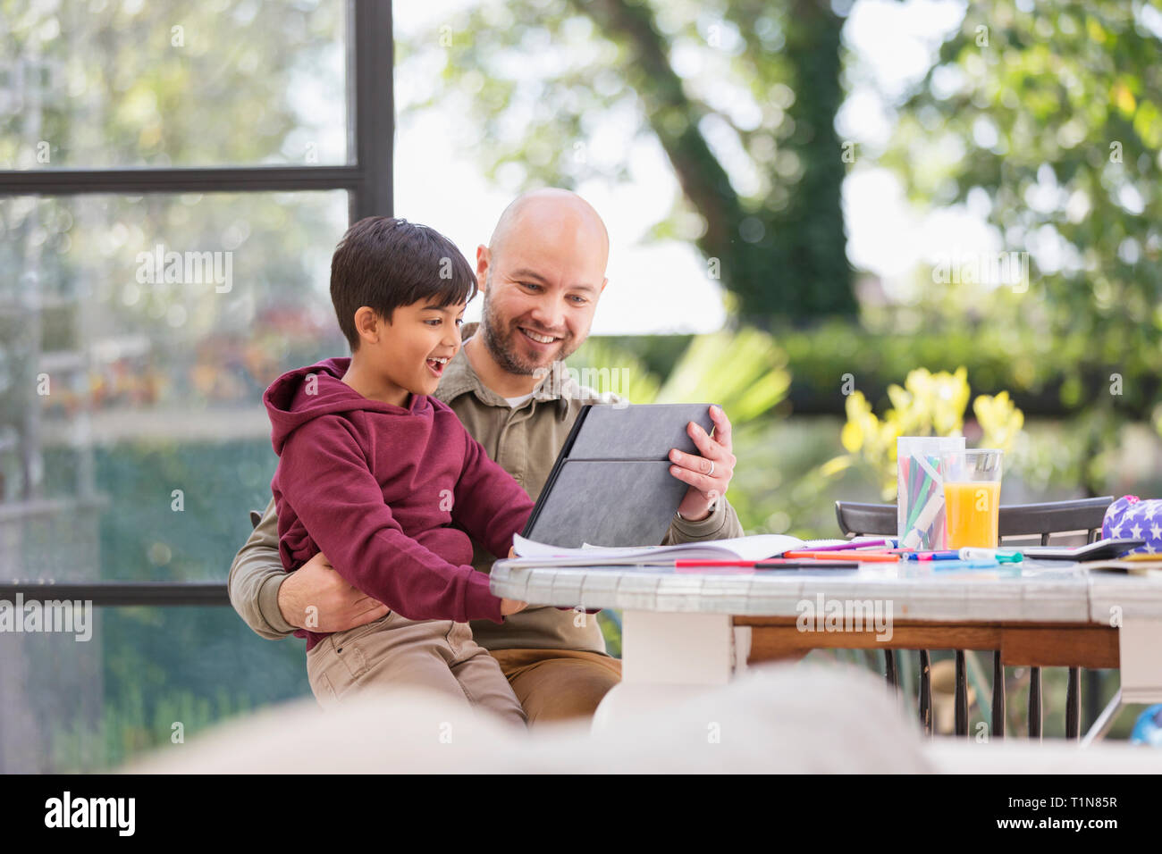 Father and son using digital tablet at table Stock Photo