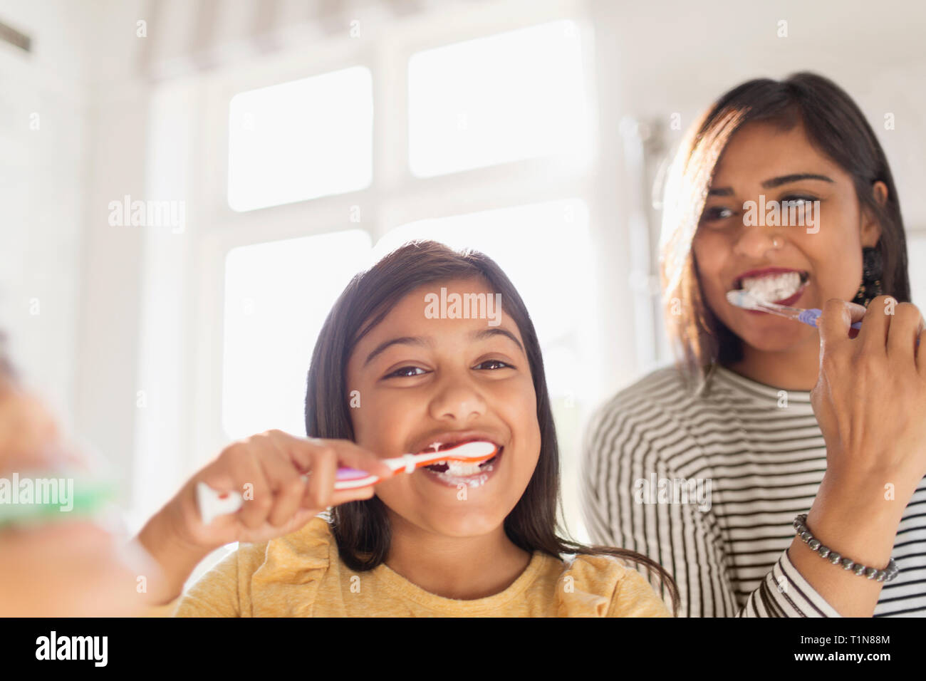 Portrait happy mother and daughter brushing teeth in bathroom Stock Photo