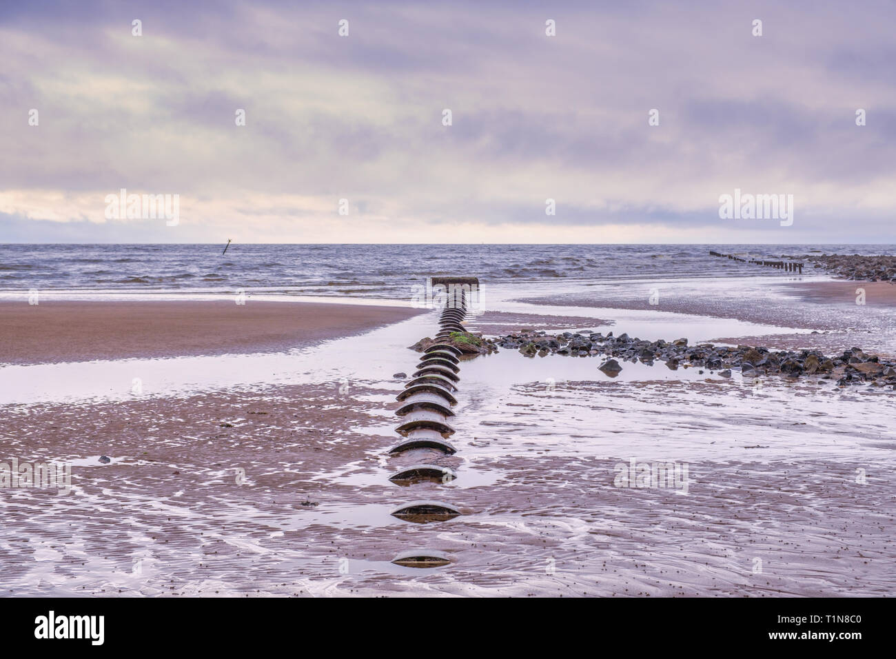 Irvine Harbour Beach Park North Ayrshire Scotland on a bright but cold March Day with an ancient partially buried sewer pipe leading out to sea. - Stock Image