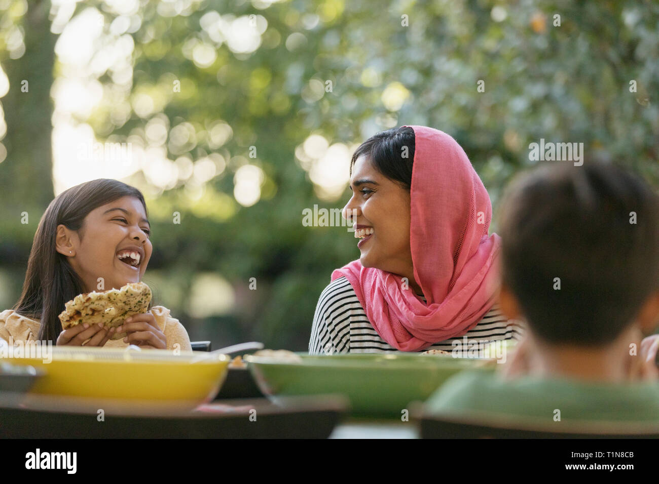 Mother in hijab and daughter laughing at dinner table Stock Photo