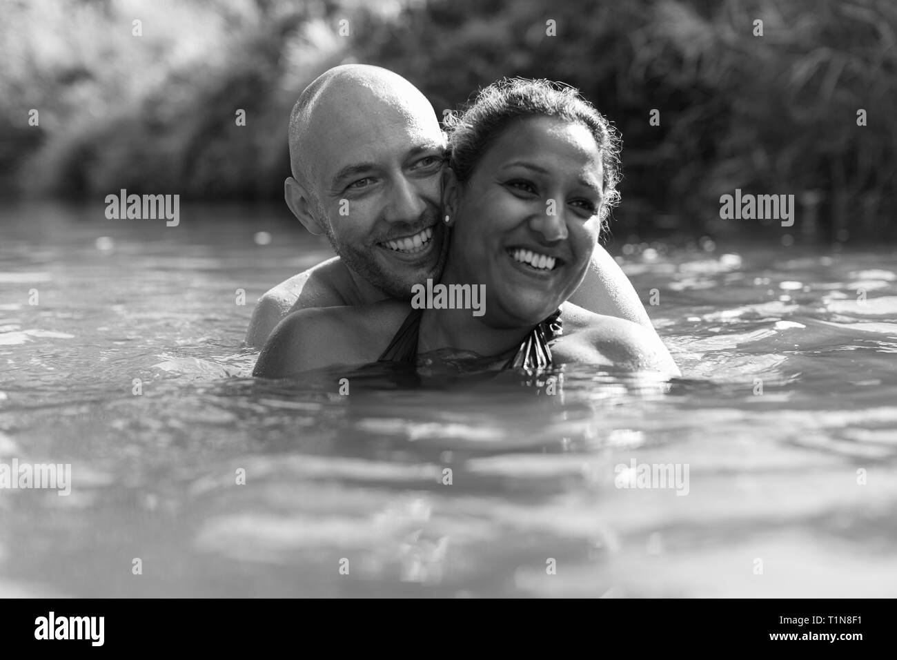Happy couple swimming in river Stock Photo