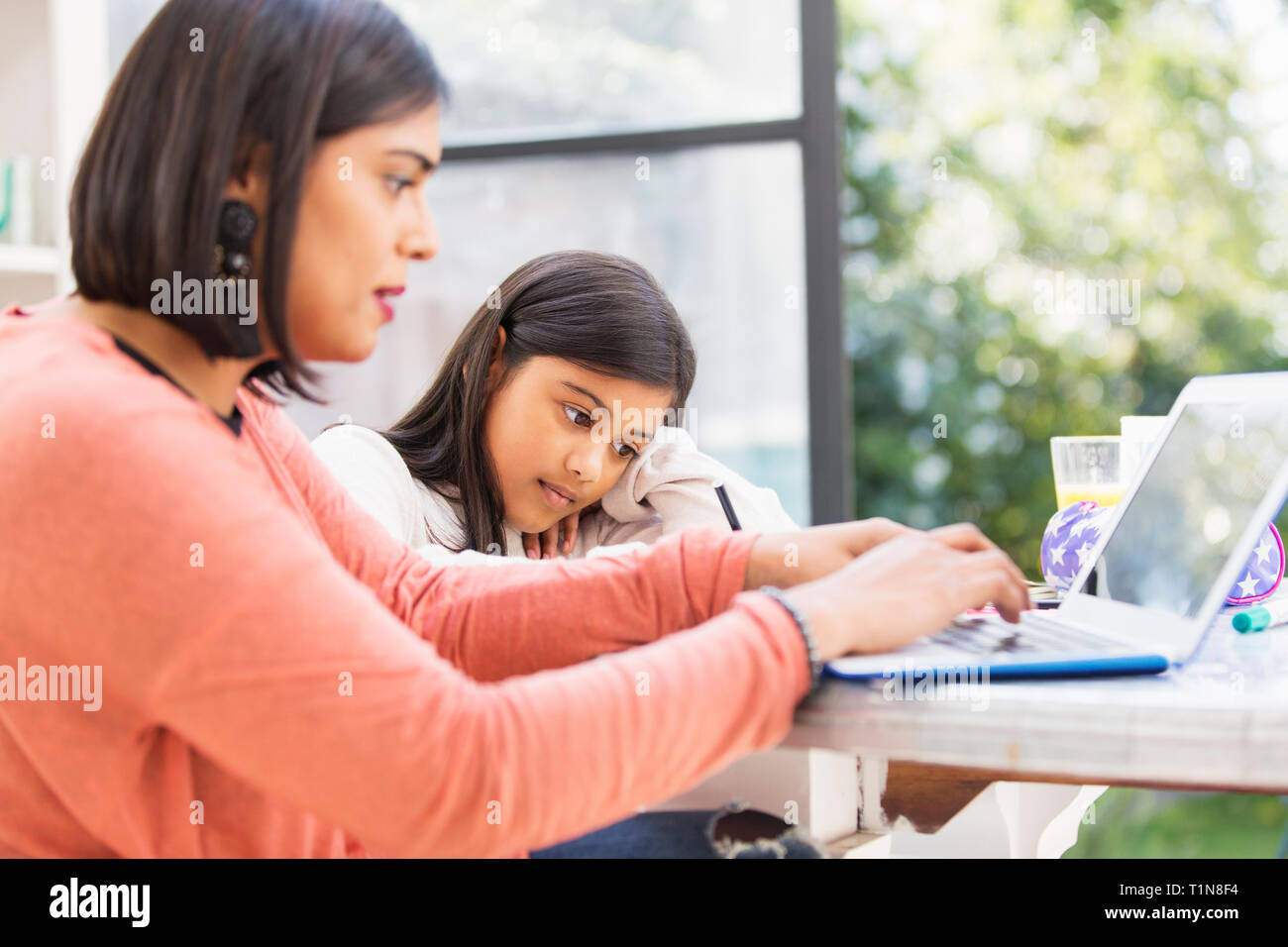 Mother and daughter using laptop, doing homework at table Stock Photo