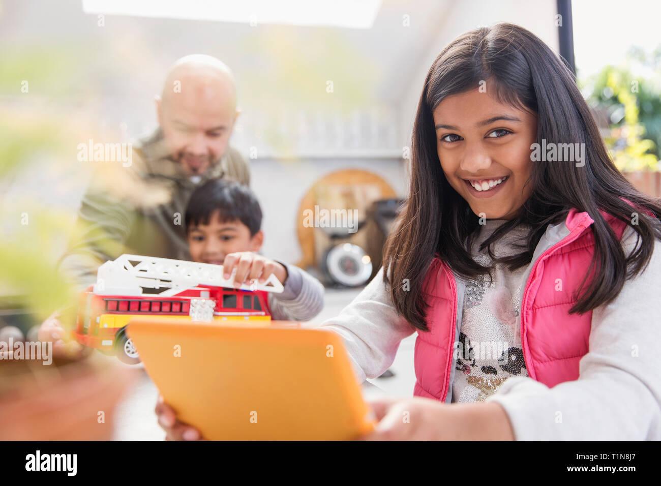 Portrait happy girl using digital tablet Stock Photo