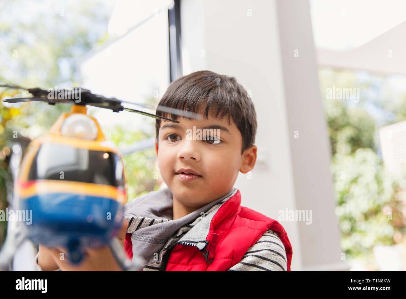 Boy playing with toy helicopter Stock Photo