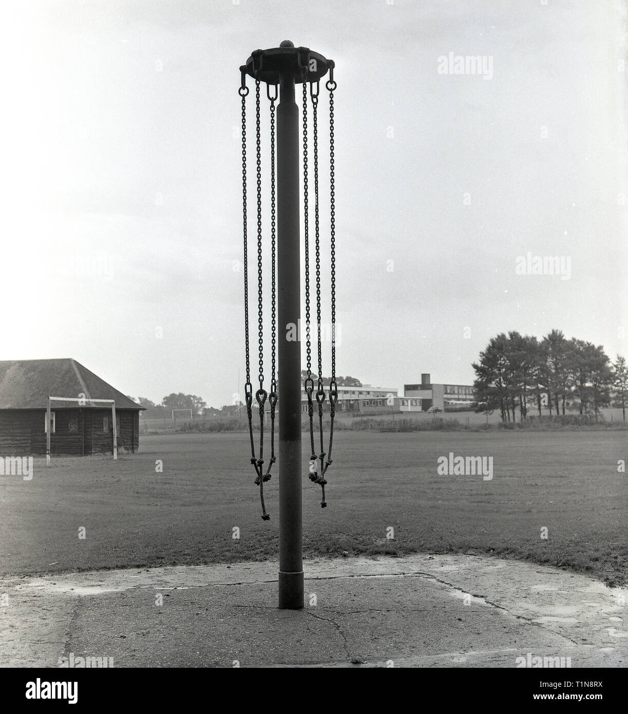 1967, a metal maypole playground swing standing at an empty