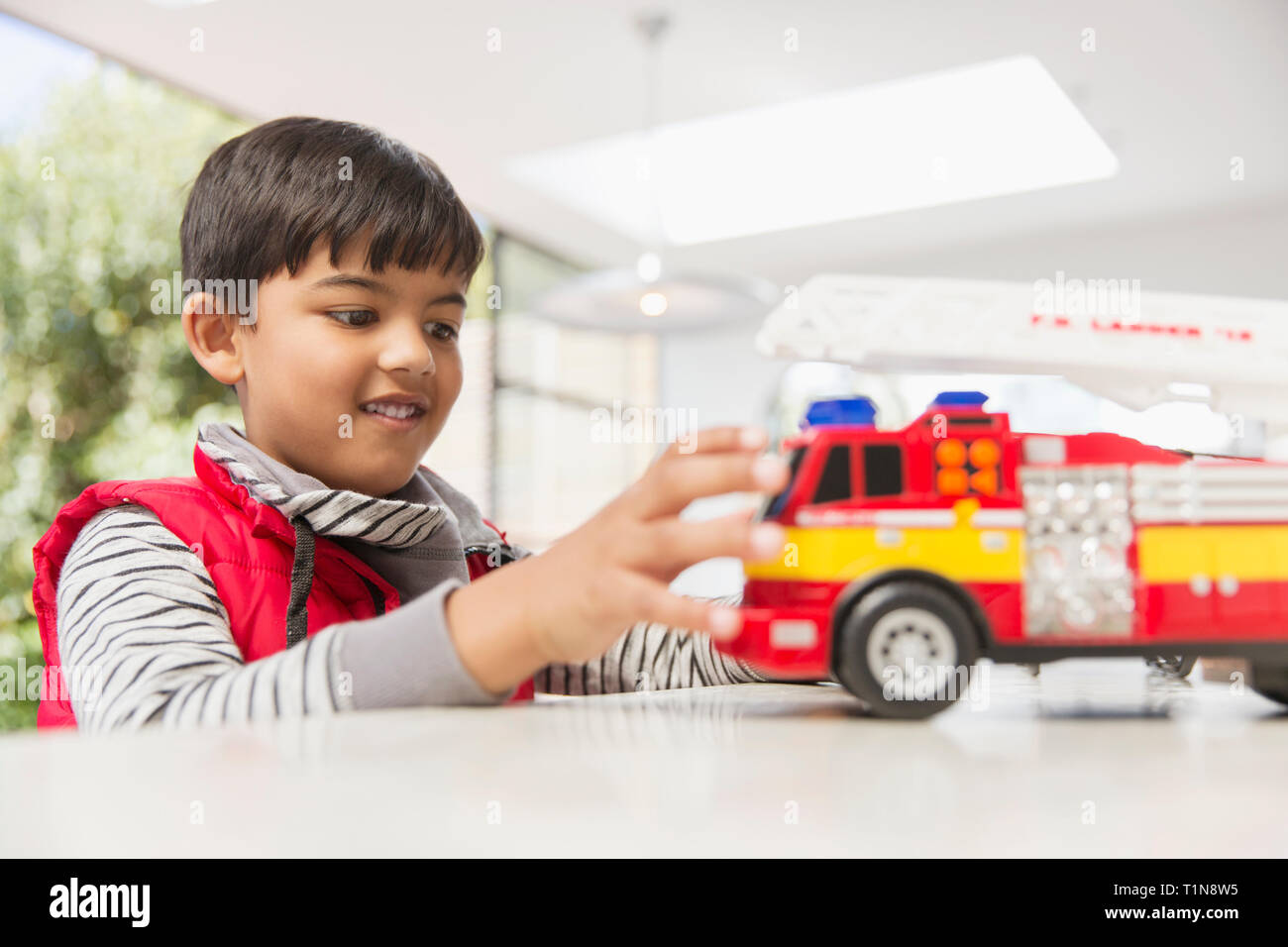 Boy playing with fire engine toy - Stock Image
