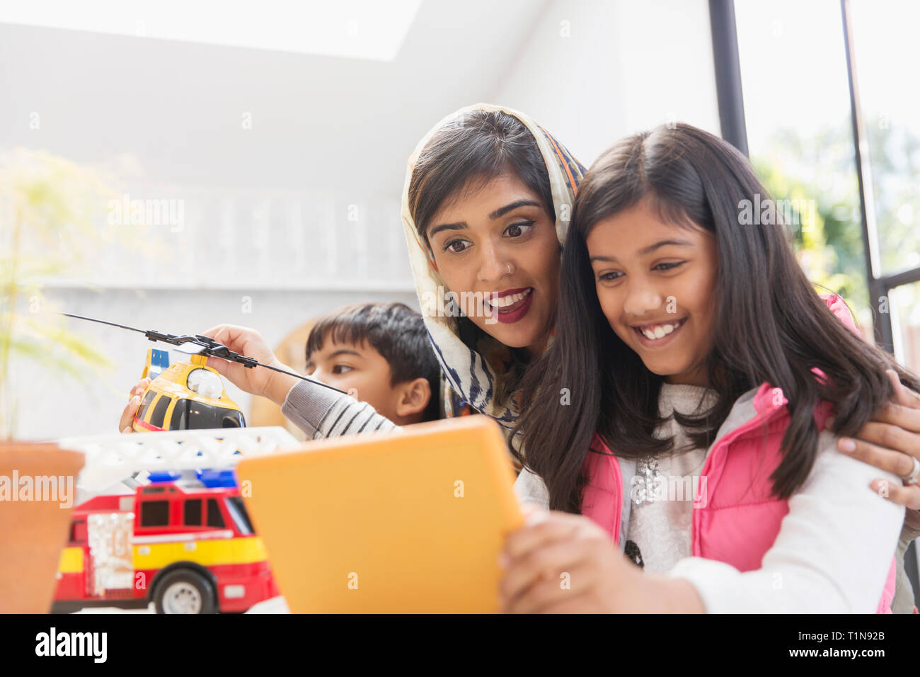 Happy mother and daughter using digital tablet Stock Photo