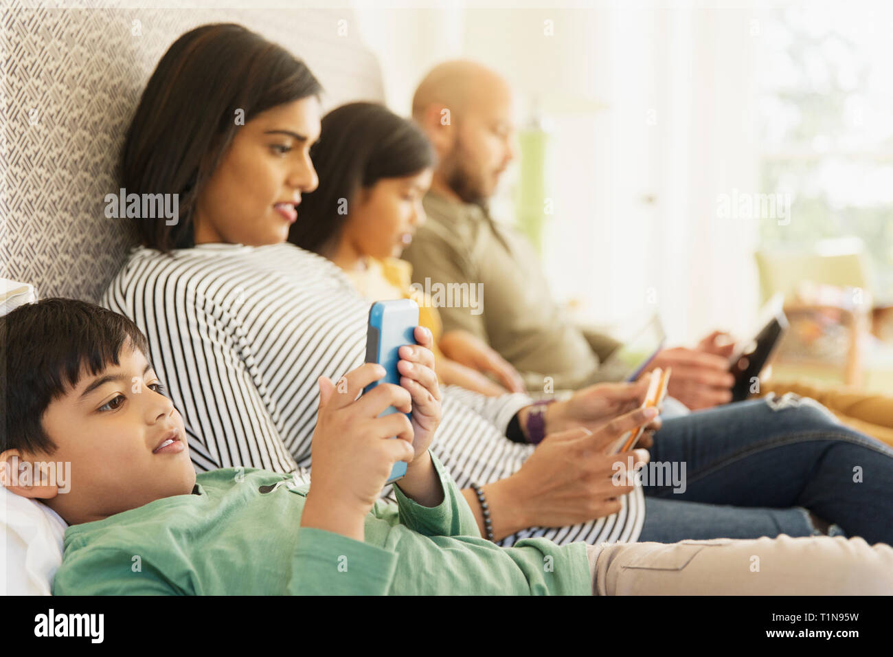 Family using technology on bed Stock Photo