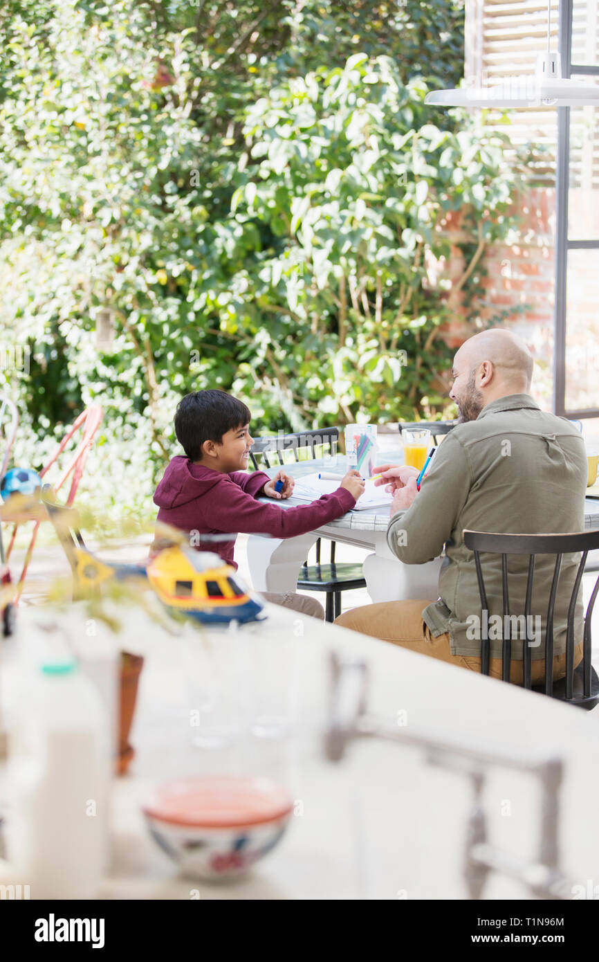 Father and son coloring at table Stock Photo