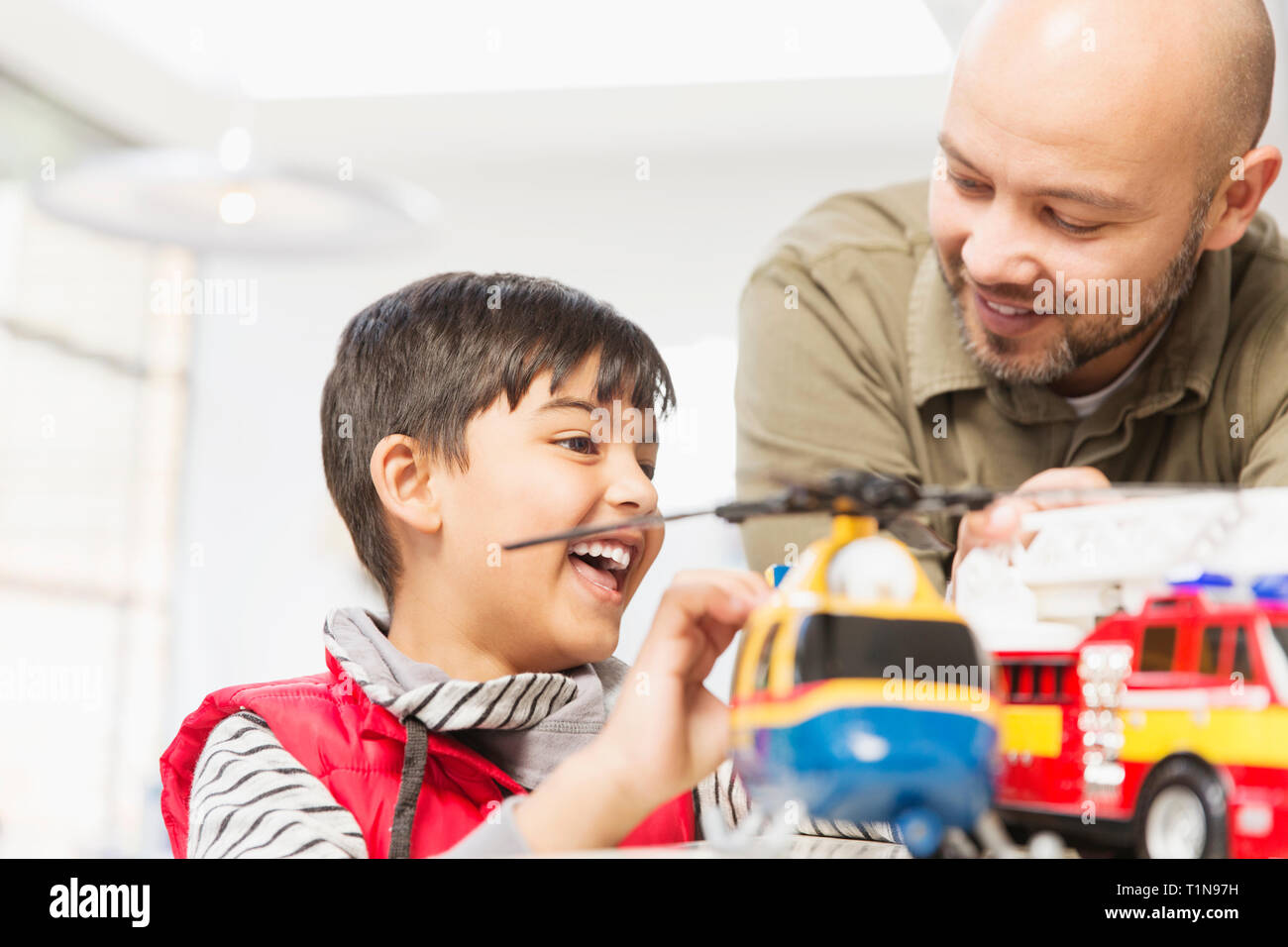 Father and son playing with helicopter and fire engine toys - Stock Image