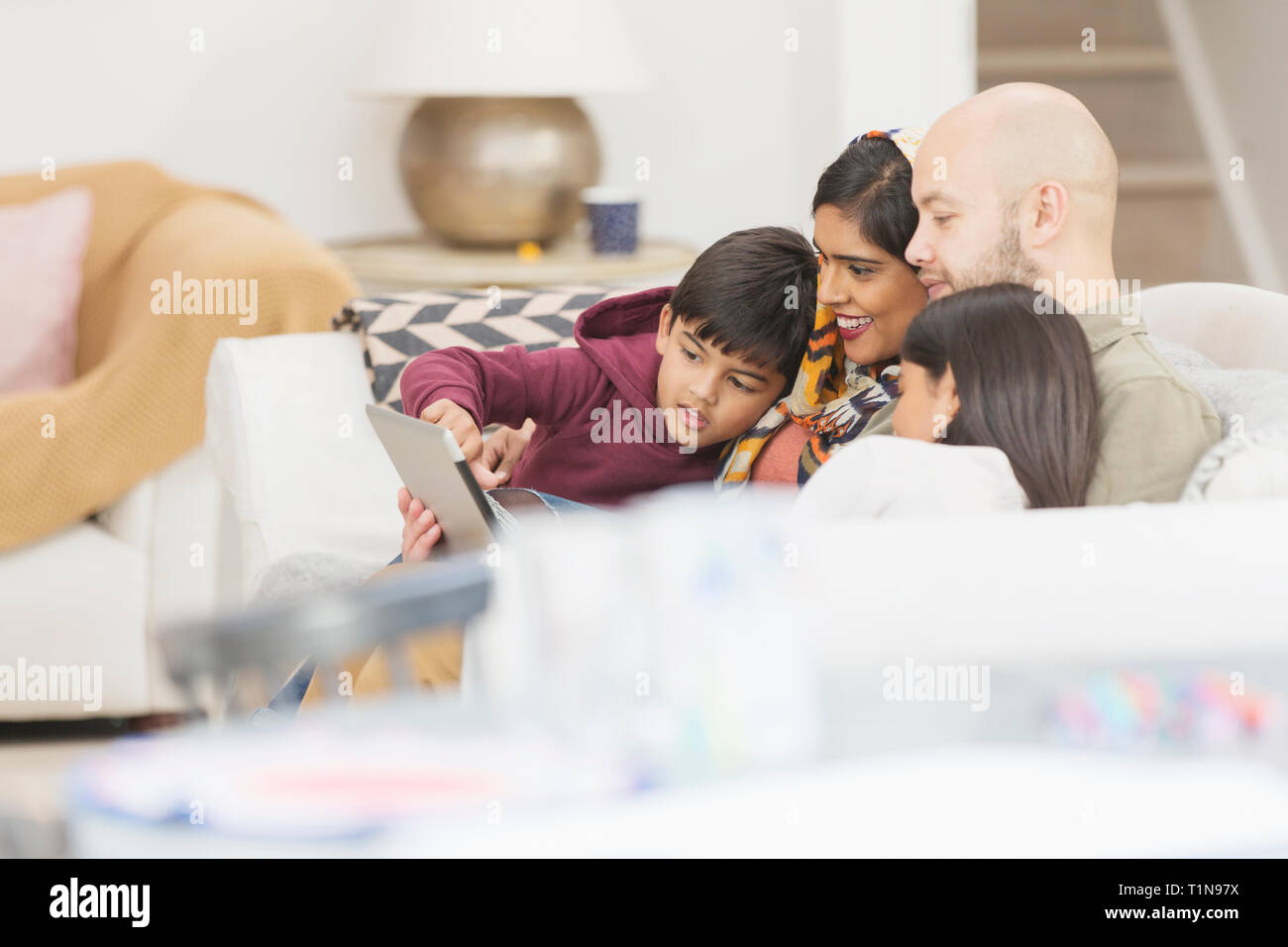 Family using digital tablet on living room sofa Stock Photo