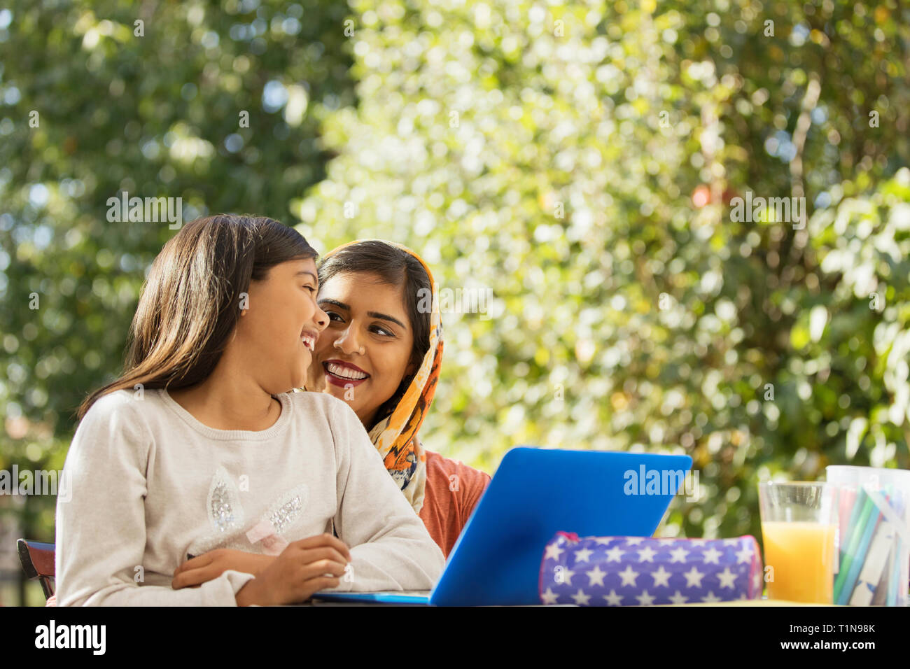 Happy mother and daughter using laptop on patio Stock Photo