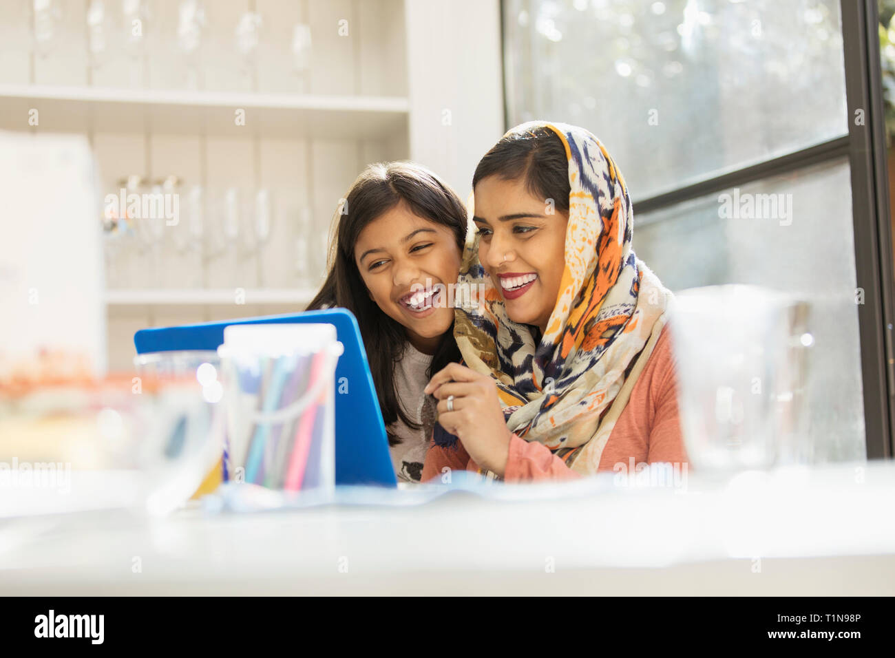 Happy mother in hijab and daughter using laptop Stock Photo