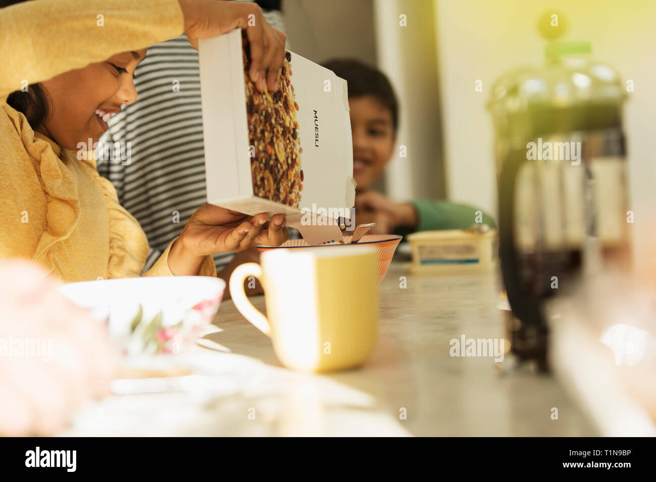 Girl pouring breakfast cereal into bowl Stock Photo