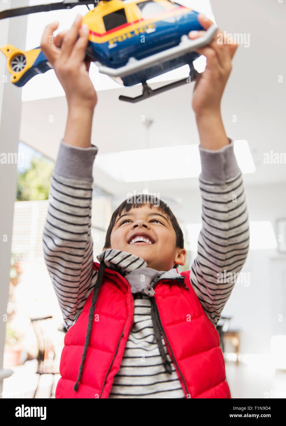 Happy boy playing with toy helicopter Stock Photo