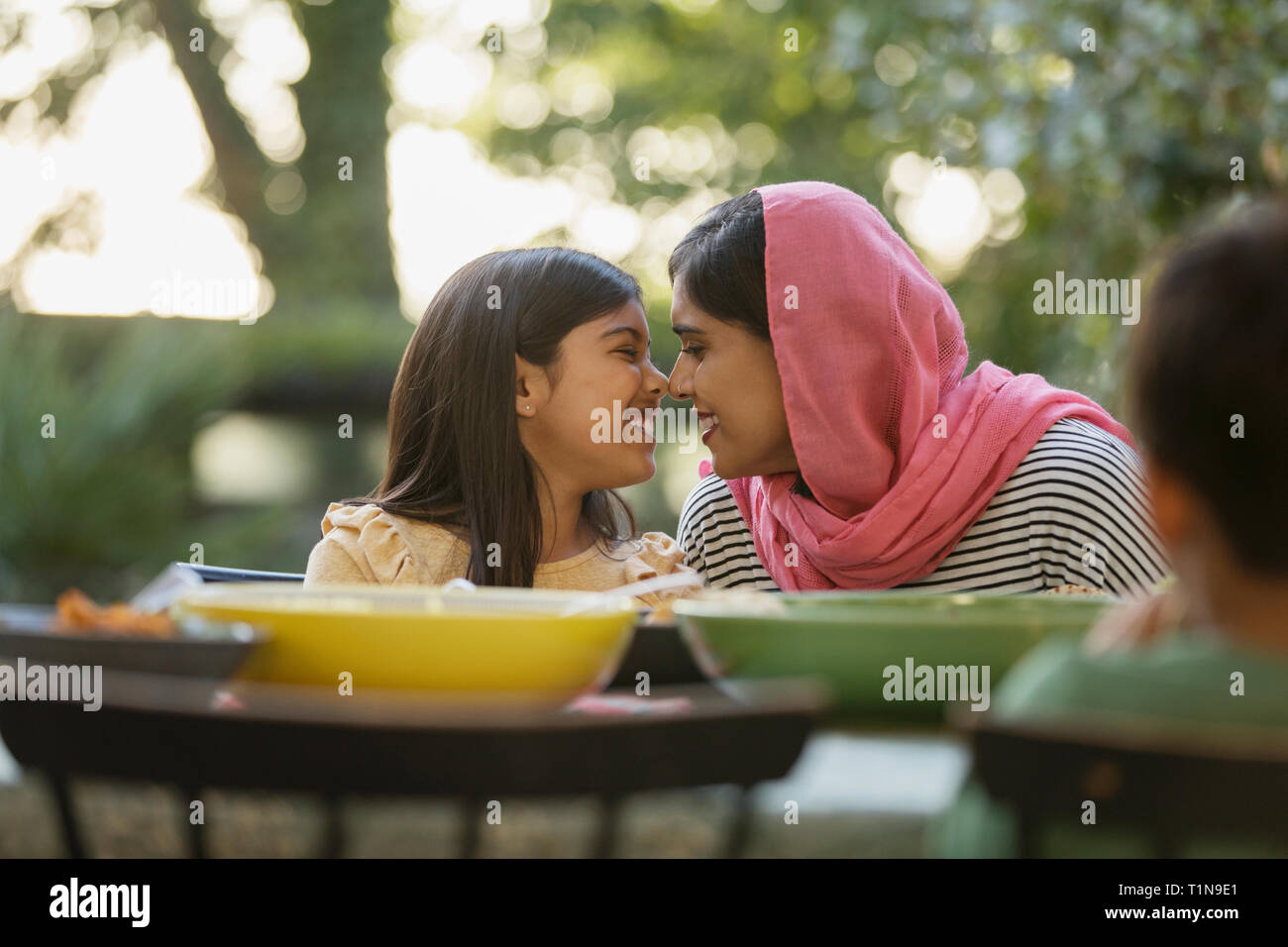 Affectionate mother in hijab rubbing noses at dinner table Stock Photo