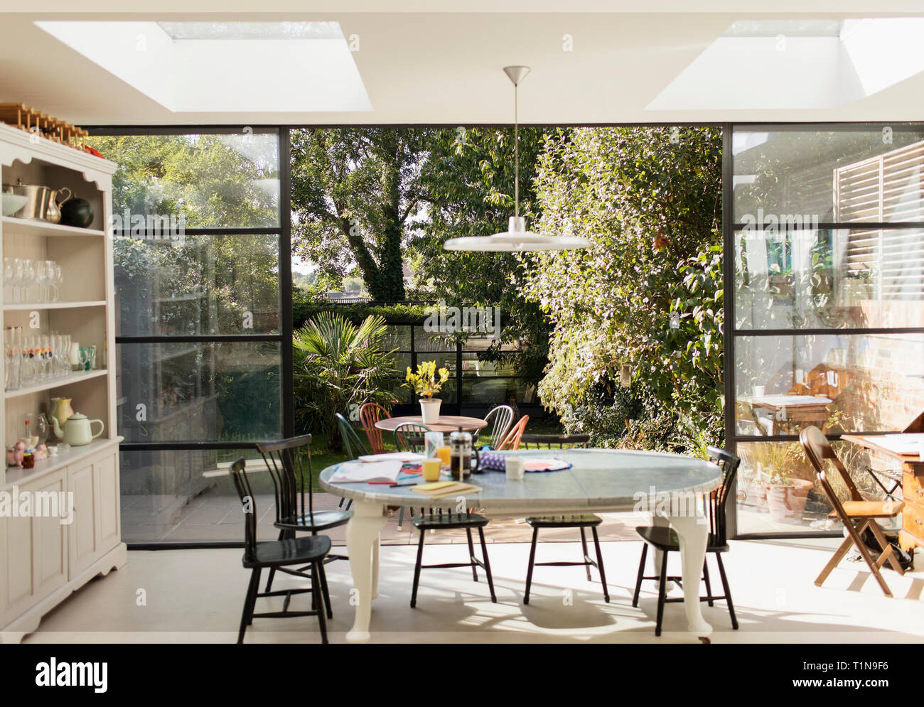 Kitchen table and patio doors open to sunny garden Stock Photo