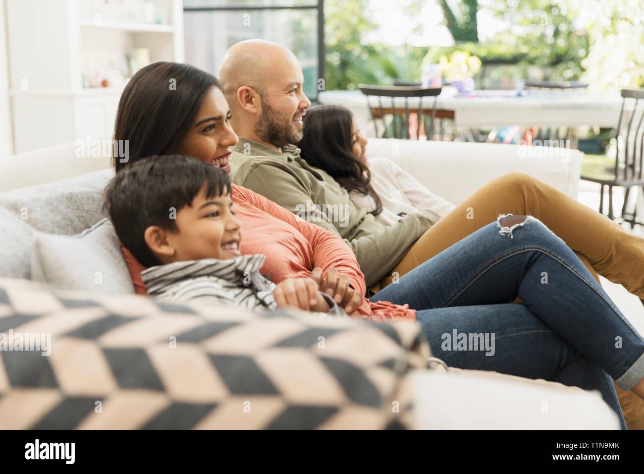 Family watching TV on living room sofa Stock Photo