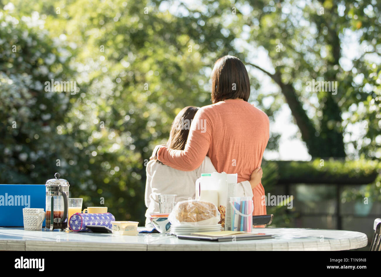 Affectionate mother and daughter on sunny morning patio Stock Photo