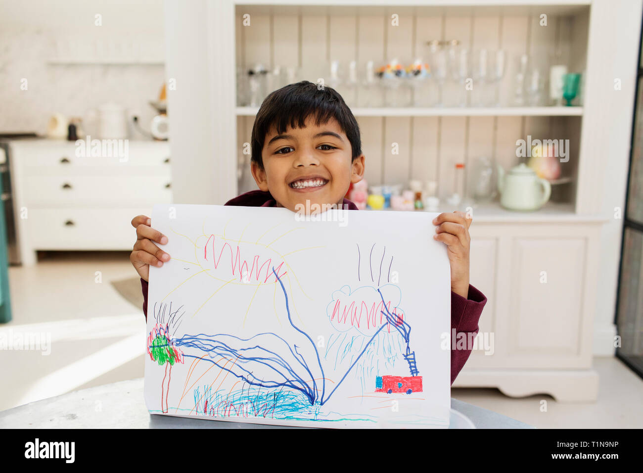 Portrait enthusiastic boy showing drawing Stock Photo