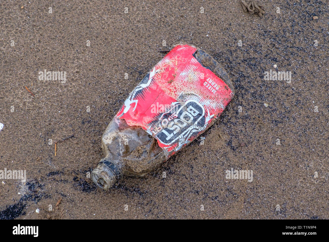 Irvine, Scotland, UK - march, 18, 2019: Environmental image of Waste with a Boost Sport Bottle that has been washed up or out being about to join the  - Stock Image