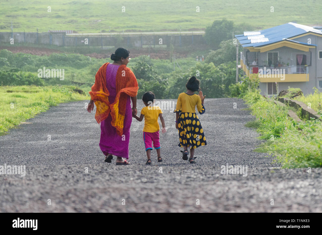 View from back of an Indian mother with her two young daughters returning home after an evening stroll. - Stock Image