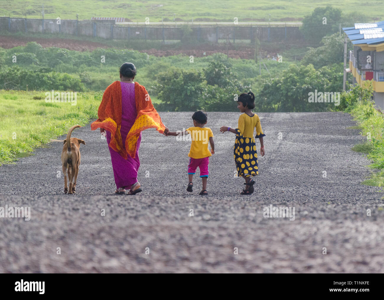 View from back of an Indian mother with her two young daughters, accompanied by a street dog, returning home after an evening stroll. - Stock Image