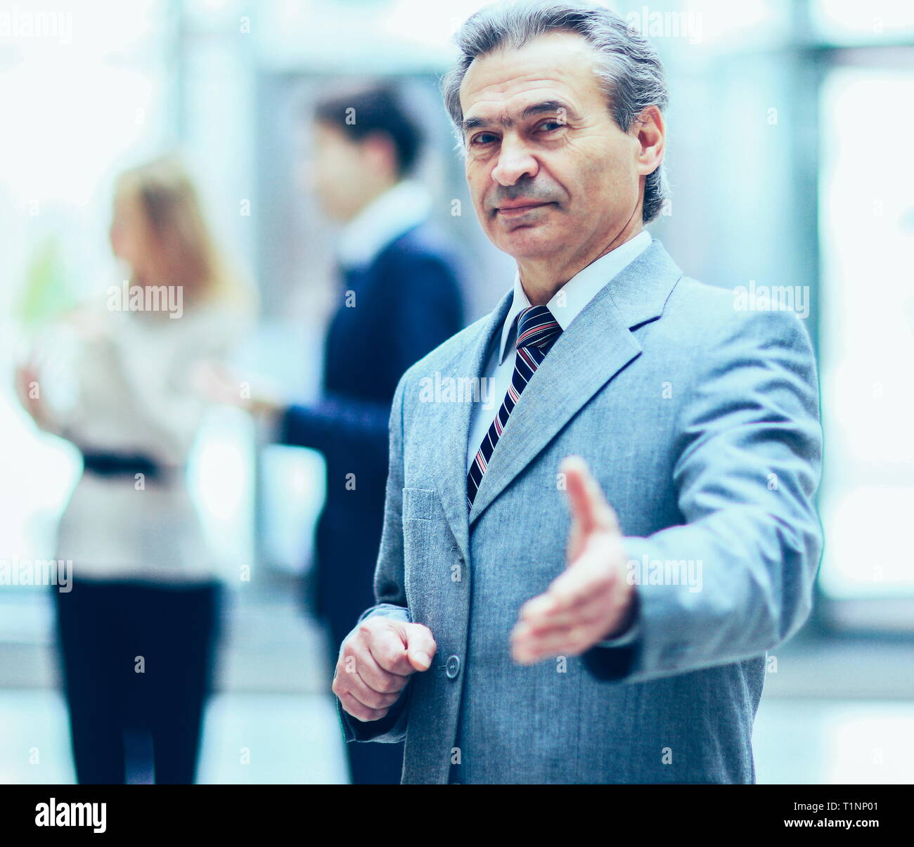 Welcoming business man ready to handshake with hand extended,   co-operate against the background of the work  his team - Stock Image