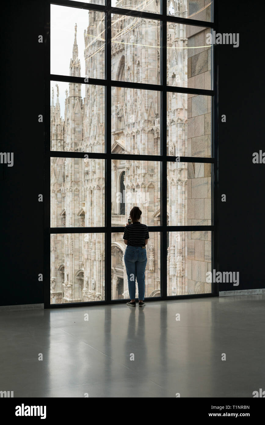 Milan. Italy. Visitor looking at the view over Piazza del Duomo from the Museo del Novecento. - Stock Image