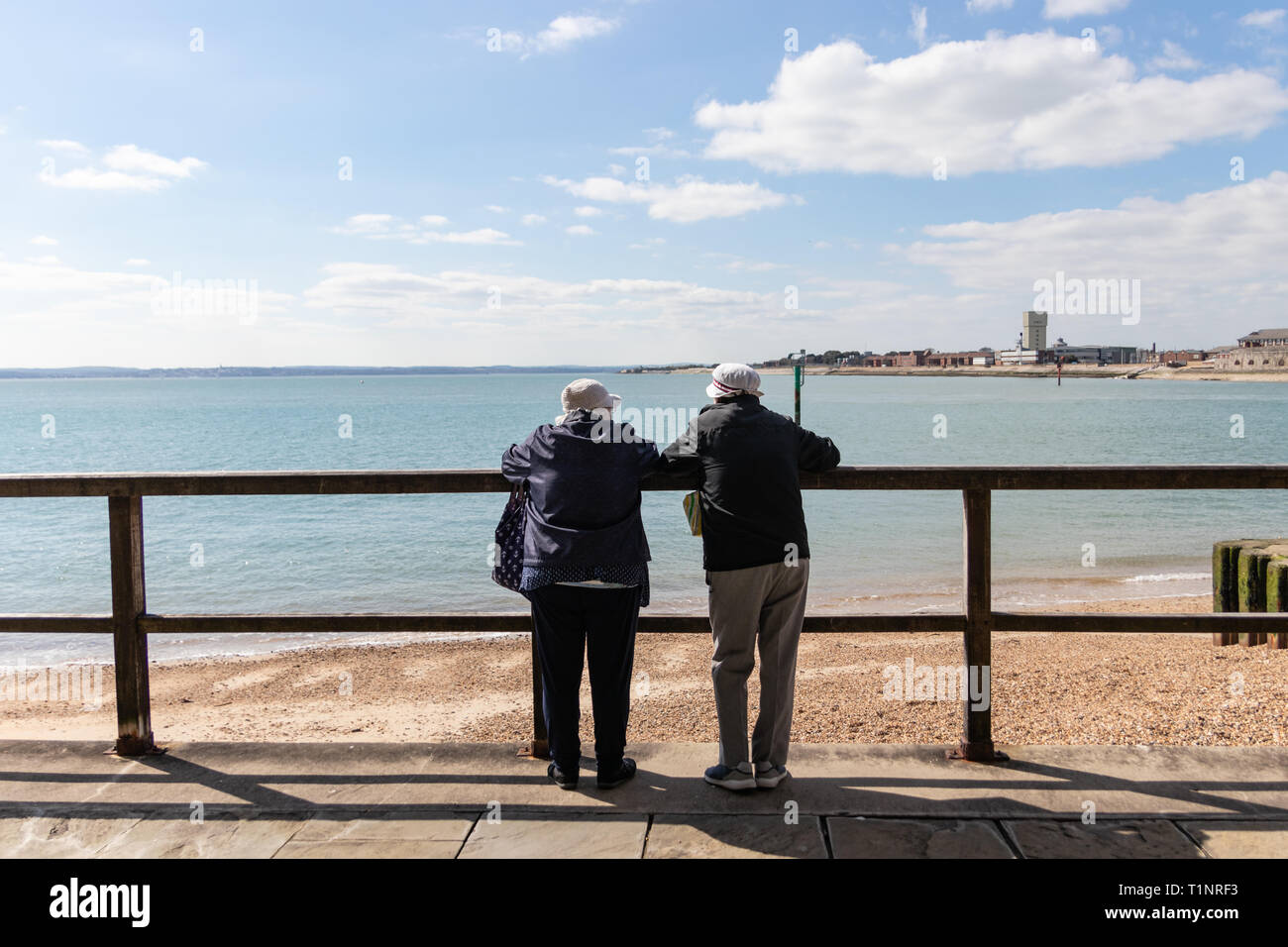 Elderly couple leaning on railings looking at the view over a pebble beach - Stock Image
