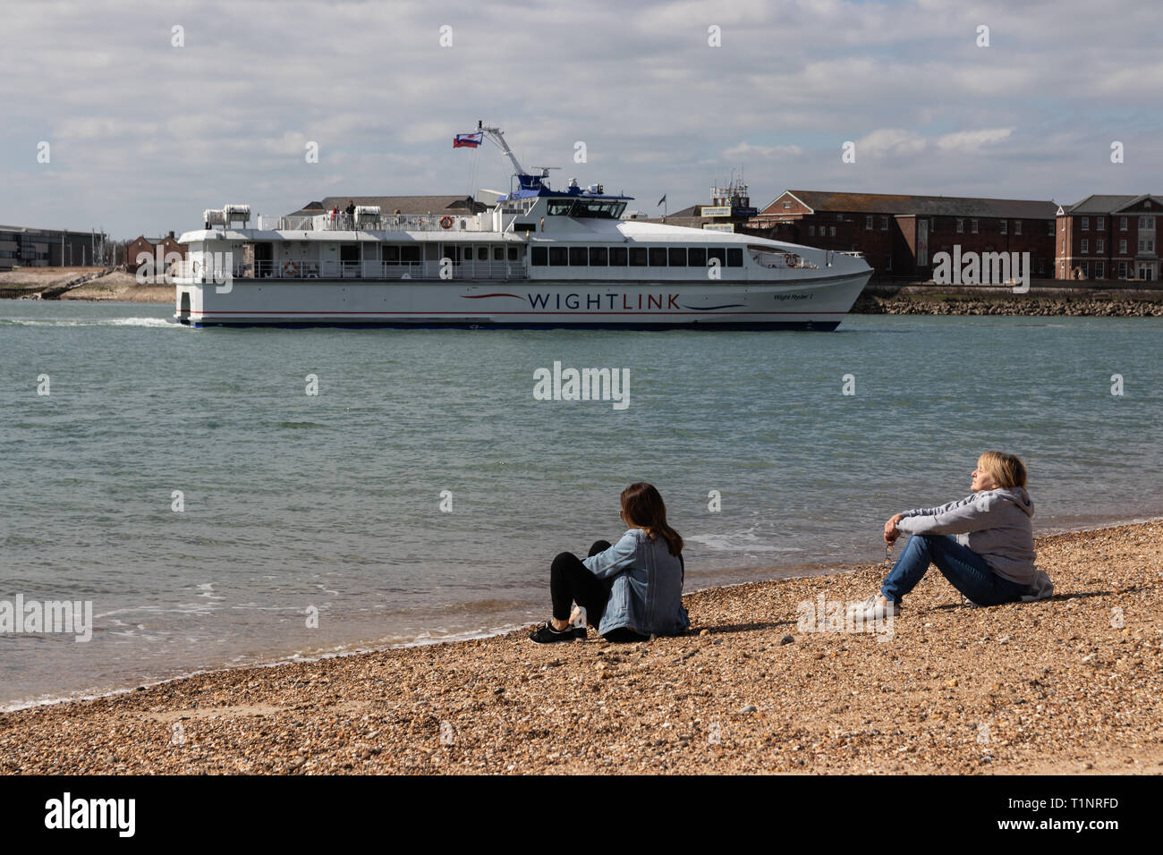 Mother and daughter enjoying the sun on the beach at Old Portsmouth pebble beach Stock Photo