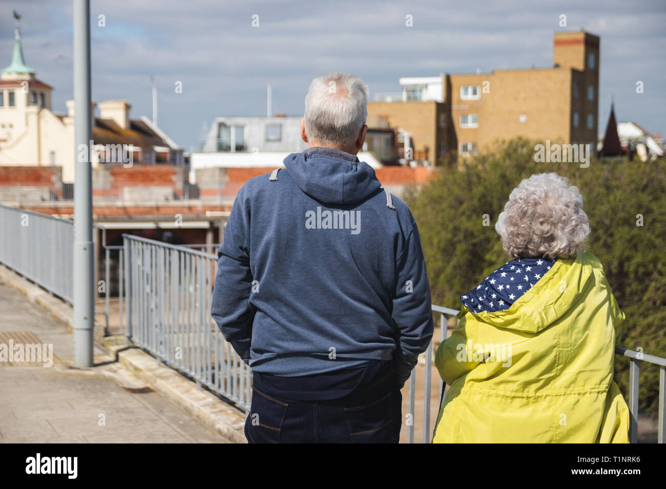Elderly couple walking together on a promenade looking at the view - Stock Image
