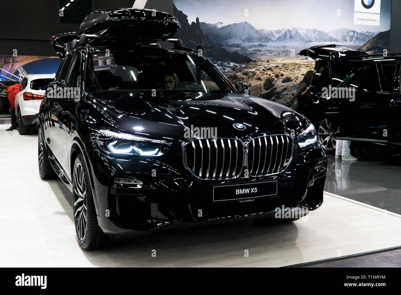 Salzburg, Austria - March 23rd, 2019: Young couple checking out the BMW X5 at the Salzburg car show - Stock Image